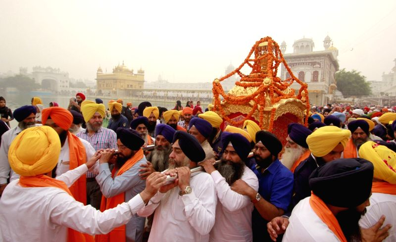 Sikh devotees carrying palanquin during a Nagar Kirtan procession on the eve of Guru Nanak Jayanti at the Golden Temple in Amritsar