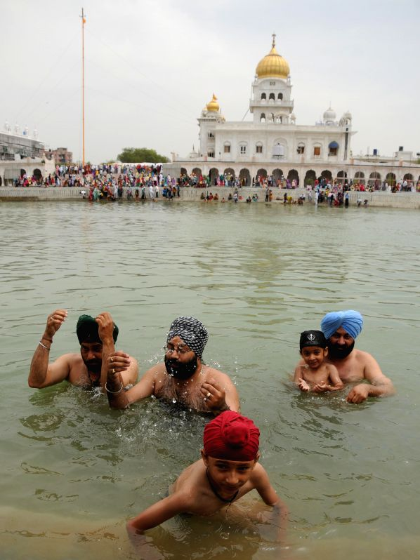 Sikh devotees take a holy dip in the 'sarovar' at Bangla Sahib Gurudwara on the eve of Baisakhi in New Delhi on April 13, 2014.