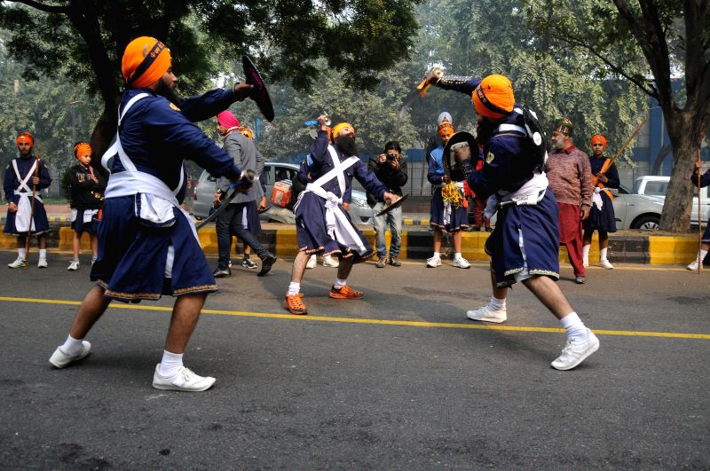 Sikh Nihangs demonstrate their skills during a 'Nagar Kirtan' (road show) organised on the 'Prakash Parv'  of  Guru Gobind Singh in New Delhi on Dec 28, 2014.