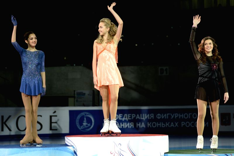 Silver medalist Evgenia Medvedeva (L) of Russia, gold medalist Elena Radionova (C) of Russia and bronze medalist Adelina Sotnikova of Russia attend the awarding ...