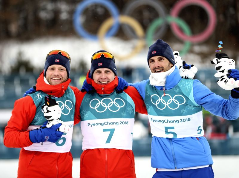 Simen Hegstad Krueger (C) of Norway and his compatriotsMartin Johnsrud Sundby (L) and Hans Christer Holundcelebrate after crossing the finish line to win gold, silver and bronze ...