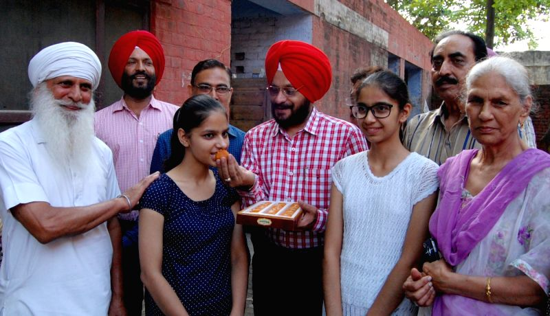 Simranpreet Kaur, who secured second rank in class X exams conducted by Punjab School Education Board in Amritsar celebrates with her family , on May 24, 2016. - Simranpreet Kaur