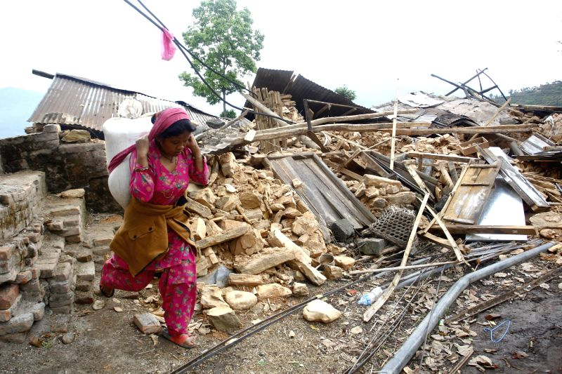 A woman carries belongings from her home after earthquake at Sindhupalchowk district, Nepal, April 29, 2015. By noon on Wednesday, more than 1,376 people ...
