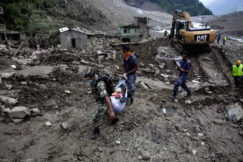 Rescuers work at the site of landslide in Sindhupalchowk, Nepal, Aug. 5, 2014. A landslide, caused by continual rainfall, hit Sindhupalchowk district in ...