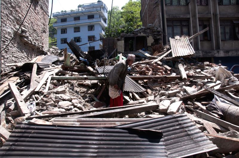 A man collects his belongings from his destructed house at Barhabisey, in Sindhupalchowk, Nepal, on May 3, 2015. At least 7,040 persons were confirmed dead ...