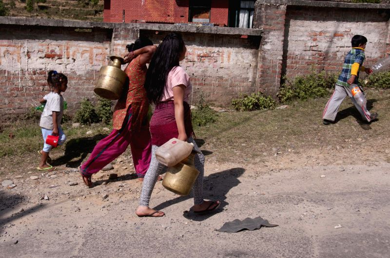 People carry empty buckets to fill water far from their houses after an earthquake in Sindhupalchowk, Nepal, May 3, 2015. At least 7,040 persons were confirmed ...