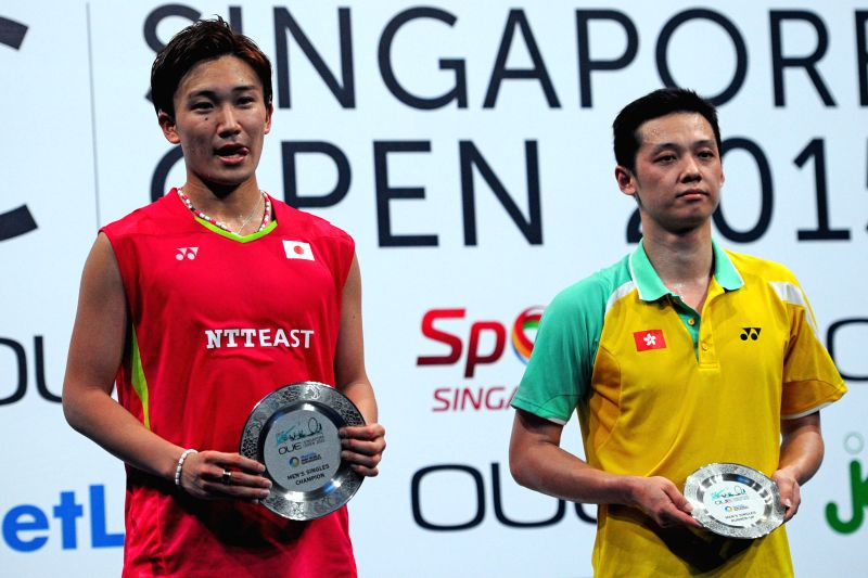Kento Momota (L) of Japan and Hu Yun of China's Hong Kong attend the awarding ceremony of men's singles final match of the OUE Singapore Open in Singapore, April ...