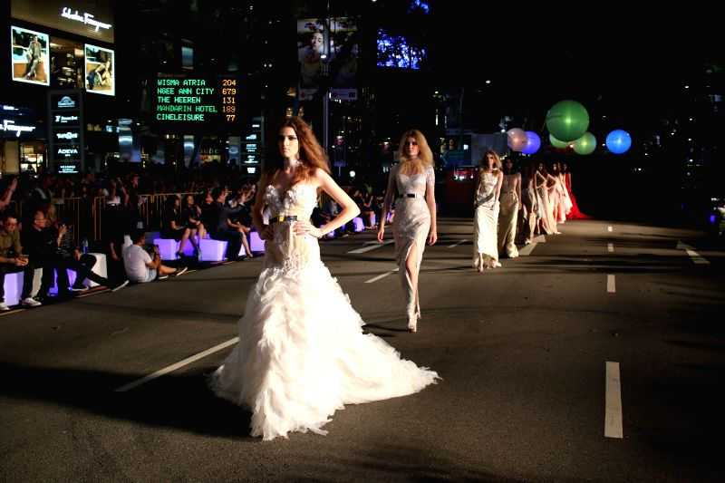 Models walk the runway on Orchard Road in Singapore, April 11, 2015. Fashion lovers and tourists have enjoyed an open-air fashion show on Singapore's iconic ...