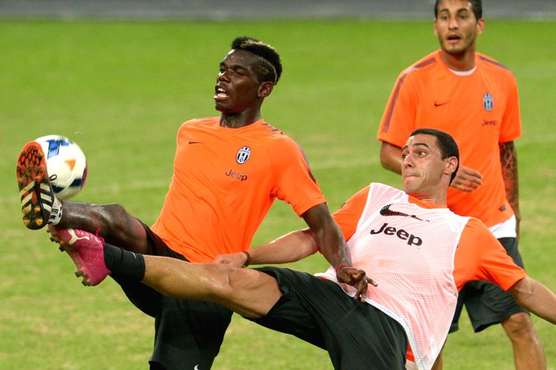 Italy's Juventus Football Club's player Paul Pogba (L) attends a pre-match training session at the Singapore National Stadium on Aug. 15, 2014. Juventus Football .