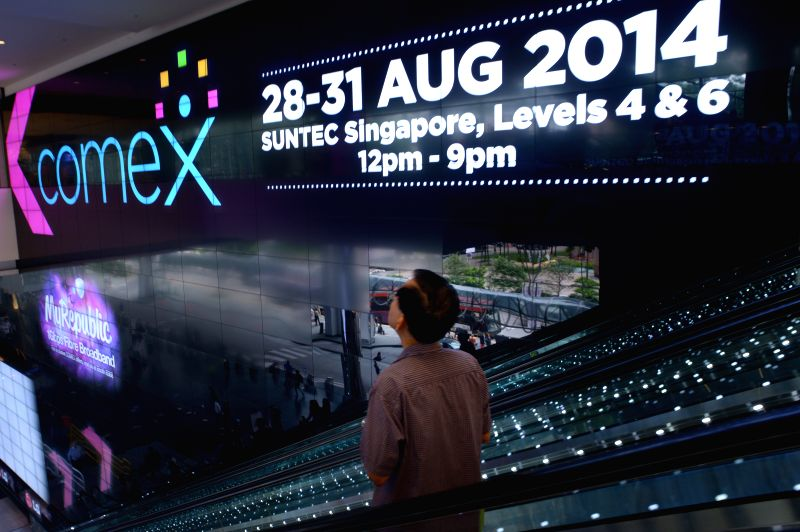 A visitor passes an advertising board during the COMEX Show in Singapore on Aug. 28, 2014. COMEX Show opened for the first day of exhibition in Singapore on ...