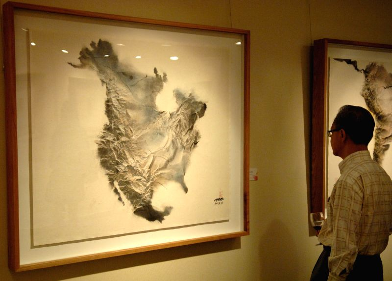 A visitor looks at an art work at the first overseas stop of The Award of Art China (AAC) Tour in Singapore, on Dec. 20, 2014. Visitors can have a glimpse of the .
