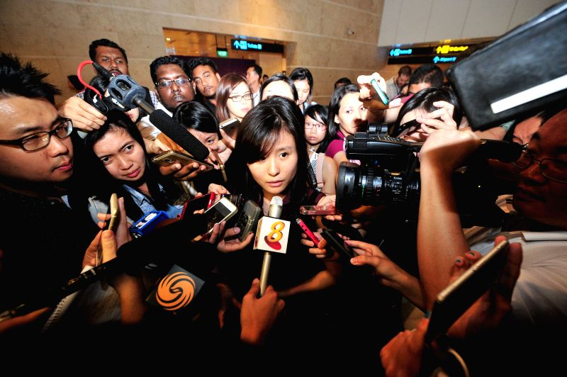 A fiancee (C) of a passenger on AirAsia flight QZ8501 speaks to the media at Singapore's Changi Airport, on Dec. 28, 2014. Malaysian Transport Minister Liow Tiong - Liow Tiong Lai