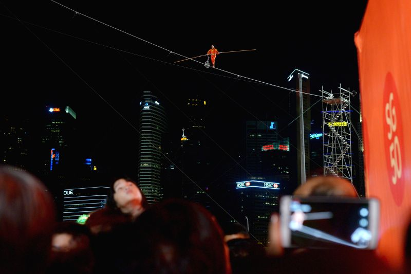 "Adili Wuxor from China's Xinjiang Acrobatic Troupe performs acrobatics on the aerial tightrope during ""River Hongbao"", an annual event to celebrate the ..."