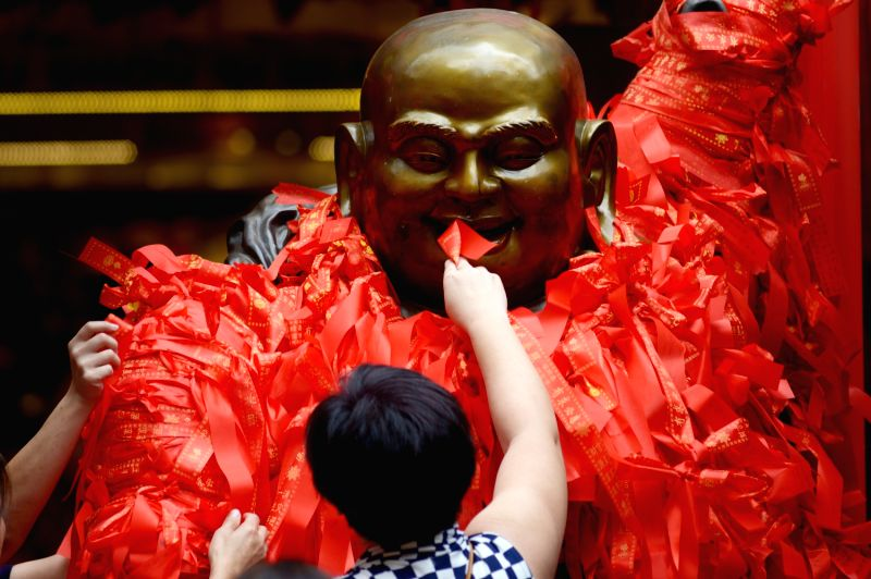 People tie ribbons of prayers on a Buddha at a Chinese Lunar New Year market in Singapore