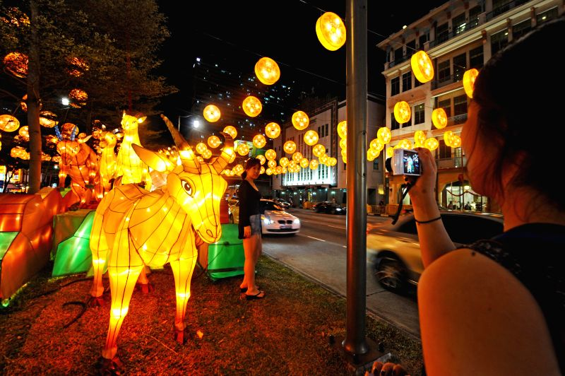 A woman poses for a photo before the lantern decorations along Singapore's Chinatown area on Jan. 27, 2015. The lantern decorations for the upcoming Chinese Lunar