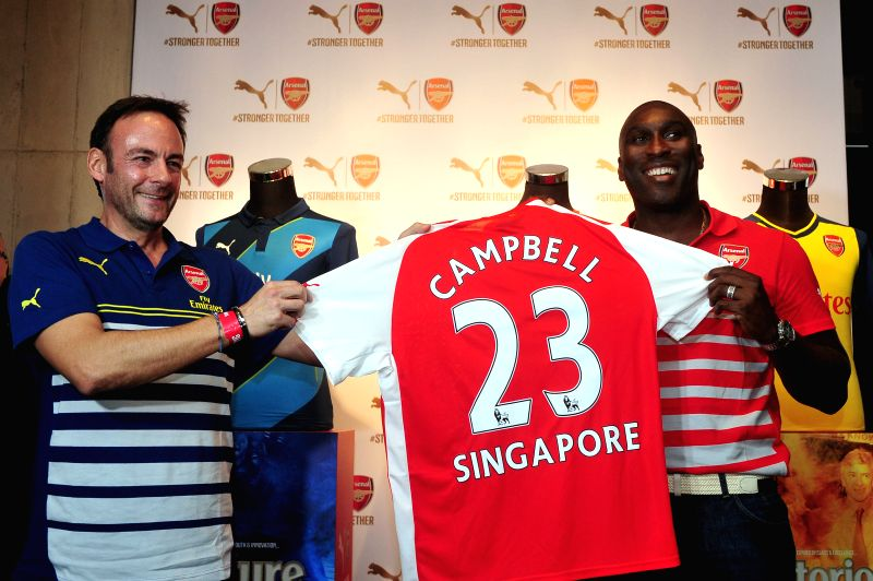 Former Arsenal player Sol Campbell (R) attends the Arsenal's new kit launch in Singapore, July 11, 2014.
