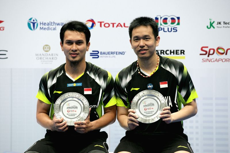 SINGAPORE, July 22, 2018 - Indonesia's Mohammad Ahsan/Hendra Setiawan (R) pose for photo during the awarding ceremony of the men's doubles final against Ou Xuanyi/Ren Xiangyu of China at the ...
