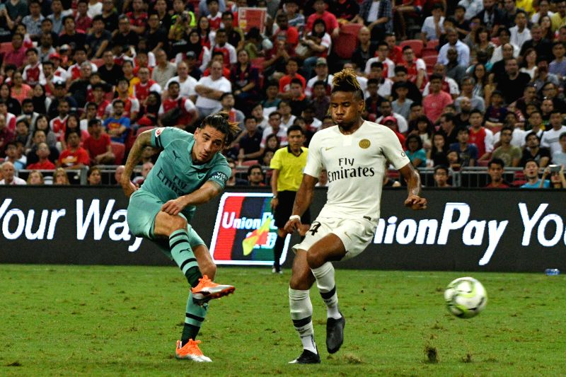 SINGAPORE, July 28, 2018 - Arsenal's Hector Bellerin (L) shoots past Paris Saint-Germain's Christopher Nkunku during the International Champions Cup soccer match held in Singapore on July 28, 2018.