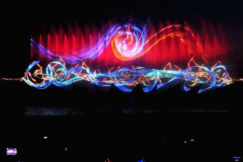 """Tourists watch the latest fireworks and fountain extravaganza """"Wings of Time"""" at Singapore's Sentosa Siloso Beach, June 20, 2014."""