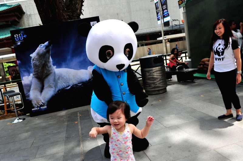 The mascot of World Wide Fund for Nature (WWF) interacts with people for the upcoming Earth Hour activities along Singapore's Orchard Road, March 12, 2015. Earth ...