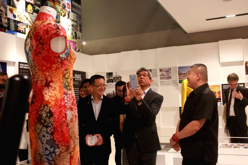 Singapore's Minister of Communications and Information Yaacob Ibrahim (C) takes a photo at the Fifty Years of Singapore Design exhibition in Singapore, March 12, ...