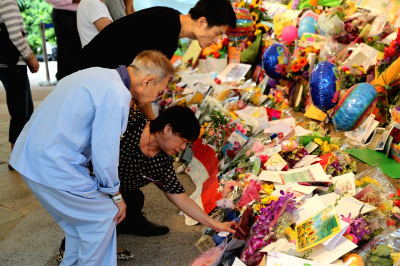 People mourn over the death of Lee Kuan Yew, former prime minister of Singapore, at the central hospital of Singapore,  March 23, 2015. Lee Kuan Yew died at 3:18 ...
