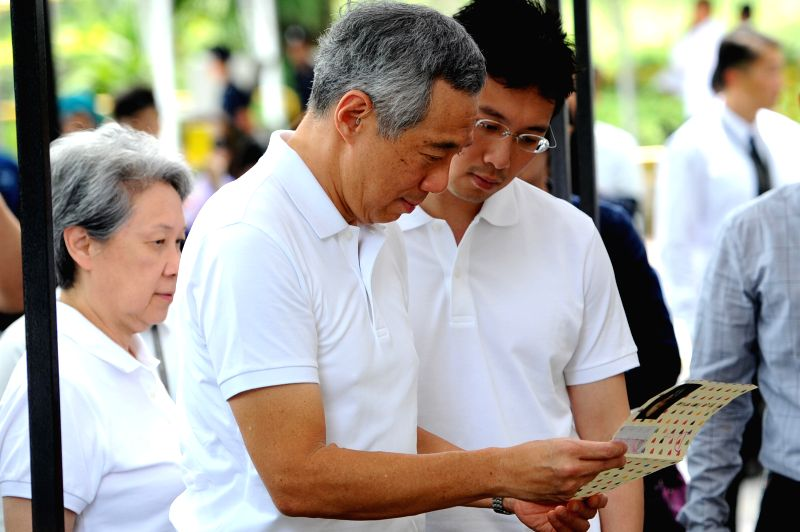 Singapore's Prime Minister Lee Hsien Loong (C) accompanied by his wife Ho Ching (L) views a condolence card at the Istana tribute site for Singapore's former ...