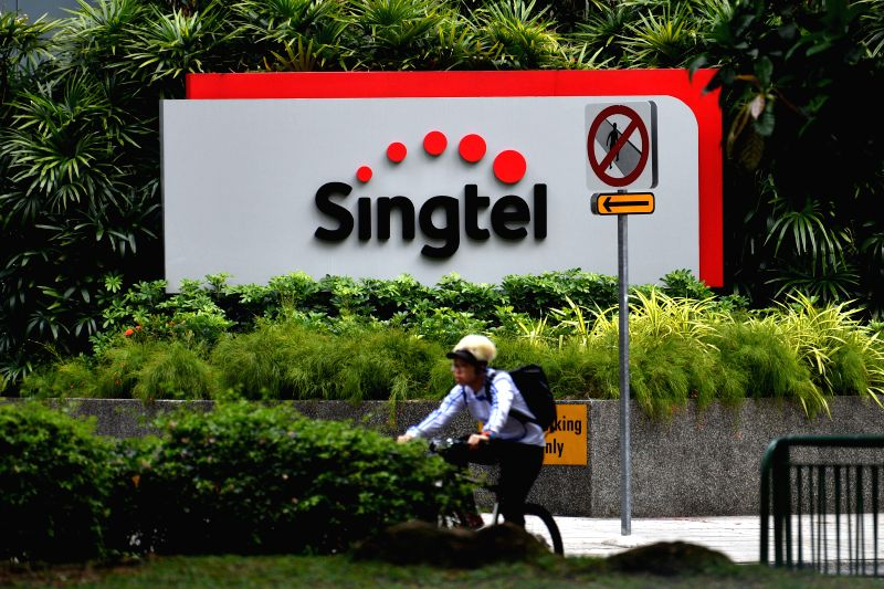 SINGAPORE, May 12, 2016 - A cyclist passes by Singtel's headquarters building in Singapore on May 12, 2016. Singapore Telecommunications Ltd, Souththeast Asia's largest telecommunications operator, ...