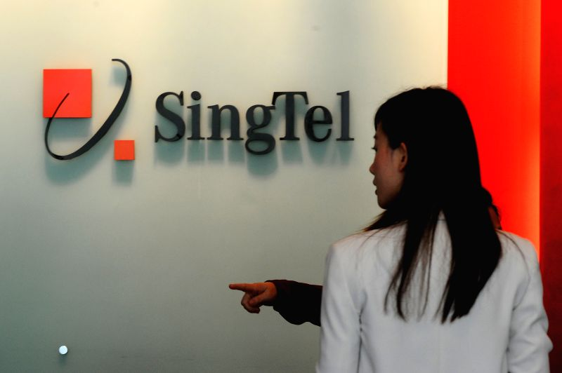 A receptionist talks to a customer at the SingTel building in Singapore's Orchard Road area, on May 15, 2014. SingTel said on Wednesday that its performance of the