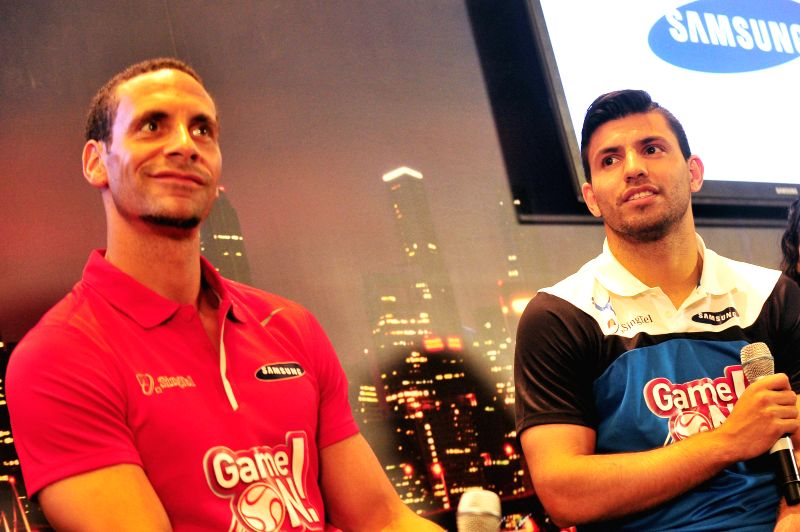 Former Manchester United football player Rio Ferdinand (L) and Manchester City's Sergio Aguero attend a press conference in Singapore on May 15, 2014. Rio ...