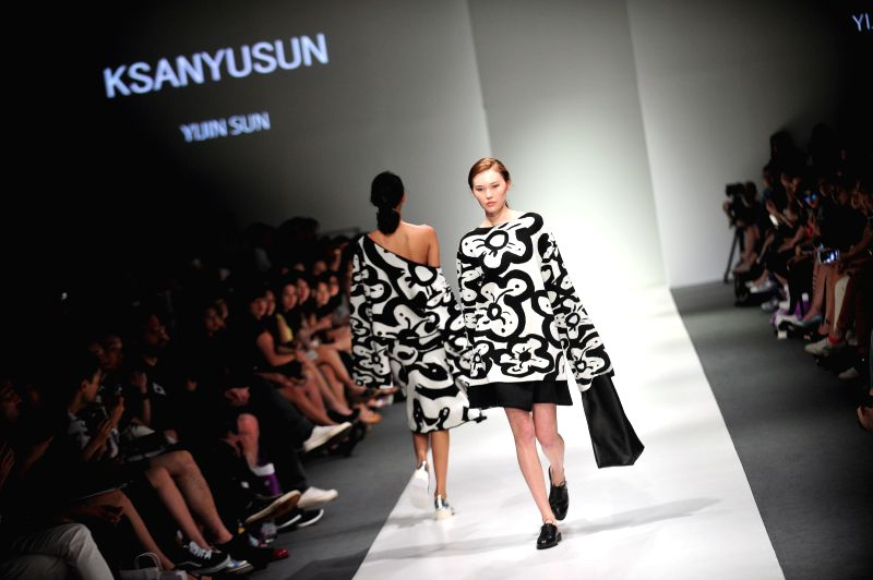 Models present creations by Chinese designer Sun Yijin during the Audi Star Creation 2014 Capsule collection at the Audi Fashion Festival held in Singapore, on May