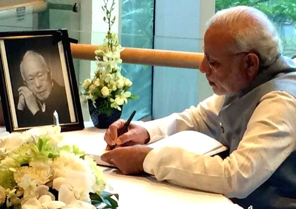 Prime Minister Narendra Modi writes in the condolence book of Singapore's first prime minister Lee Kuan Yew, in Singapore on March 29, 2015. - Narendra Modi