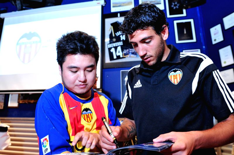 Spanish club Valencia's captain Dani Parejo (R) signs autographs for a fan after a press conference in Singapore, Sept. 2, 2014. Singapore-based businessman Peter - Dani Parejo