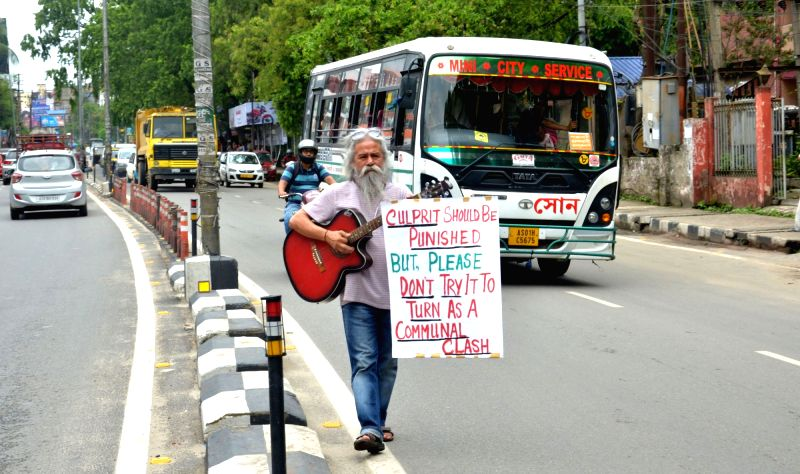 Singer and musician Kishore Giri plays a guitar as he stages a demonstration against the lynching of two Guwahati-based youths in Karbi Anglong district by villagers who mistook them to be ...