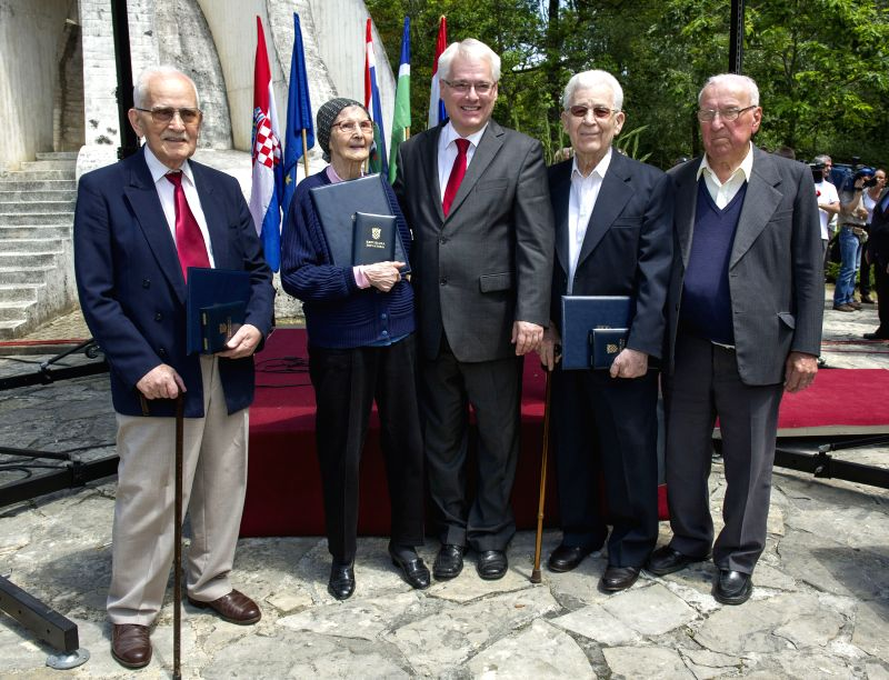 Croatian President Ivo Josipovic (C) poses for a photo with decorated anti-fascist veterans during a memorial ceremony in Brezovica Forest near Sisak, Croatia, June ..