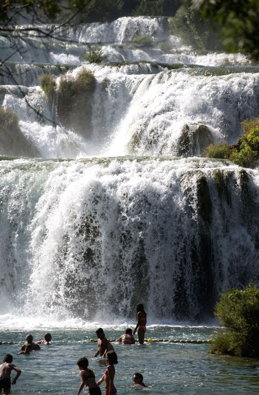 People play with water in front of the Skradinski Buk waterfall at the Krka National Park, one of Croatia's best-known nature sites and tourist destinations, in ...