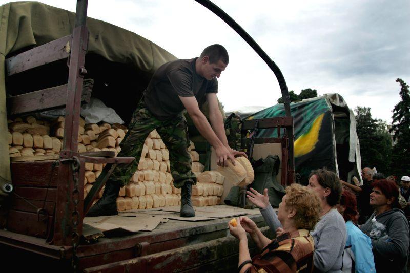 A Ukrainian soldier distributes food to residents in Slavyansk, Ukraine, July 6, 2014. Ukrainian troops have regained control over the eastern city of Slavyansk, a