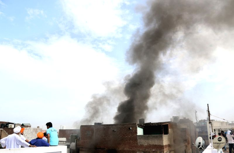Smoke billows out of a building behind Gurudwara Sis Ganj Sahib after a fire broke out at Kinari Bazaar in New Delhi on June 8, 2017.