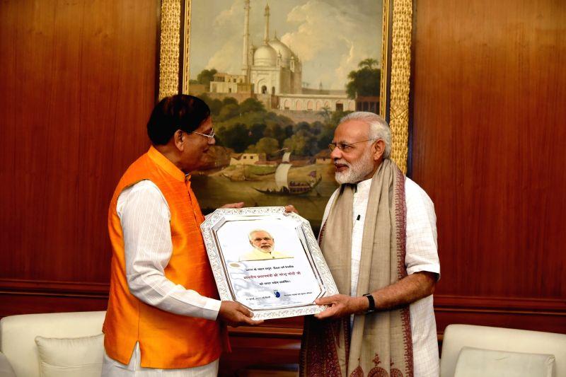 Social service organisation Sulabh International founder Bindeshwar Pathak felicitates Prime Minister Narendra Modi at the Prime Minister's Office in New Delhi on Aug 18, 2017. - Narendra Modi and Bindeshwar Pathak