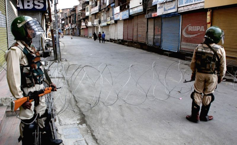 Soldier stand guard on a Srinagar road as authorities imposed restrictions in the areas of the city following the arrest of JKLF chairman Mohammad Yasin Malik on June 4, 2016. - Malik