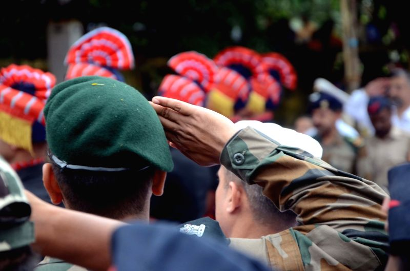Soldiers and police officials pay tributes to Major Kaustubh P. Rane ahead of his last rights, in Maharashtra's Thane on Aug 9, 2018. Thousands of people, including grieving family members, ...