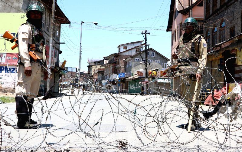 Soldiers man a Srinagar road as authorities in the Kashmir Valley imposed curfew-like restrictions to prevent separatist-called protests against the killing of a youth in security firing ...