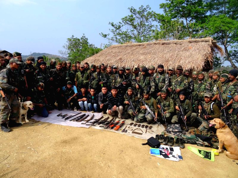 Soldiers of 15th battalion of Assam Rifles (AR) pose for photograph with the apprehended militants of Bru National Army and the recovered arms and ammunition at Kholakhal in Cachar district of Assam .
