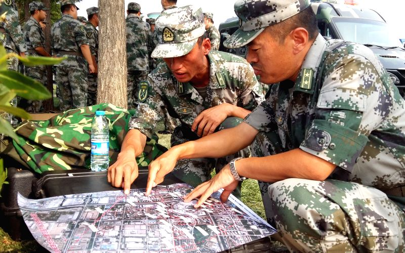 Soldiers of National Nuclear Biochemical Emergency Rescue Team prepare to launch a rescue mission at the core area of explosion site in Tianjin, north China, Aug. ...