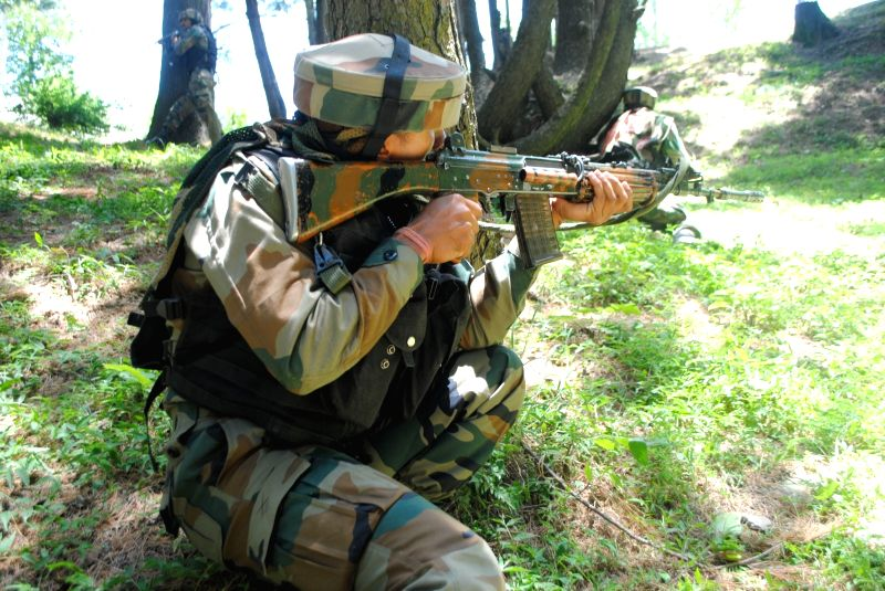 Soldiers take position during an encounter with militants in Jammu and Kashmir's Naugam district on June 8, 2017. Two militants and a soldier were killed during an ongoing operation near the ...