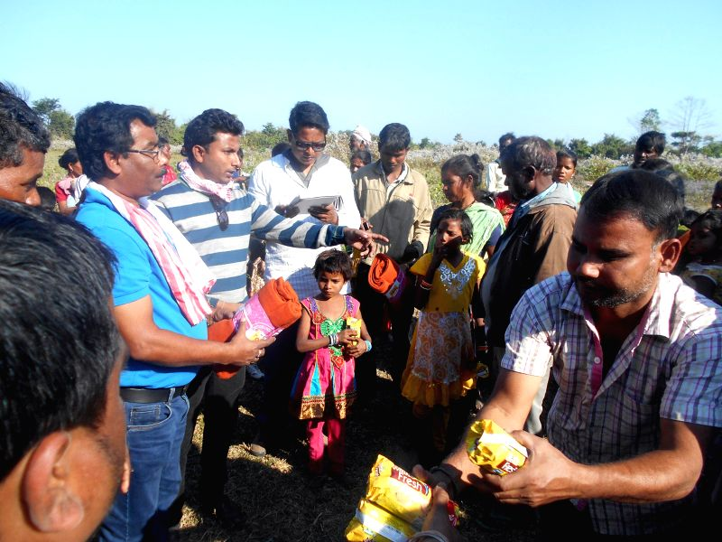 Members of Assam College Teachers Association distribute relief material to people living in a relief camp, about 20 kms away from Dhekiajuli in Sonitpur district of Assam  on Dec 30, 2014.