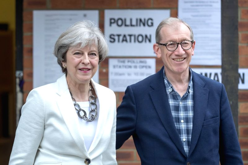 SONNING (BRITAIN), June 8, 2017 Britain's Prime Minister and leader of the Conservative Party Theresa May (L) and her husband walk out from the polling station after casting their ballots ...