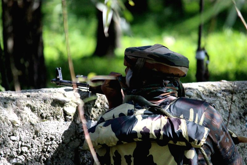 :Sopore: A soldier takes position during a gunfight with militants in in Behrampora village of Jammu and Kashmir's Baramulla district on Aug 3, 2018. Two militants were killed in the encounter ...