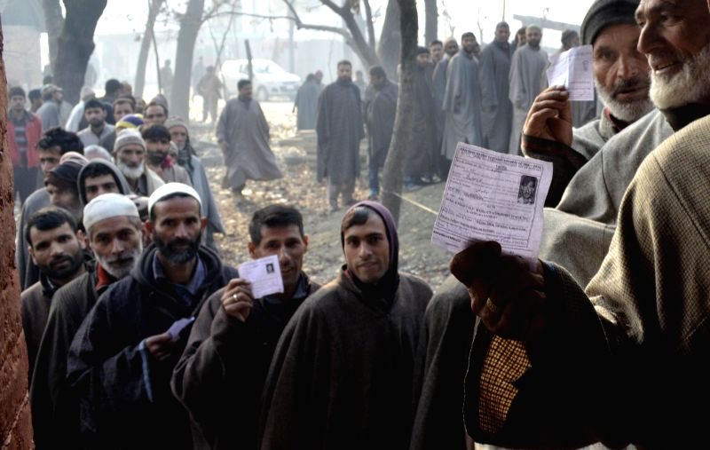 People queue-up to cast their votes during the third phase of Jammu and Kashmir assembly polls Nahidhal near Sopore on Dec 9, 2014.