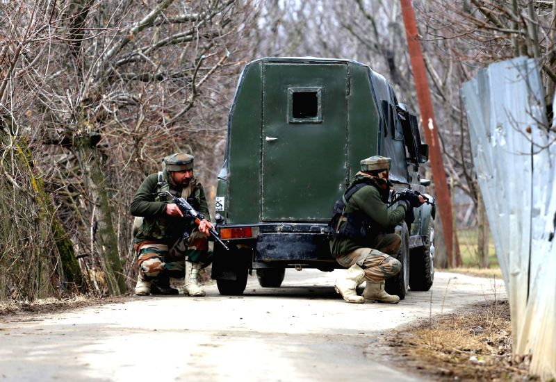 Soldiers take position during a gun-battle with militants at Rehmatabad village in Jammu and Kashmir's Sopore district on Feb 21, 2015. Two foreign guerrillas belonging to the Lashkar-e-Taiba ...